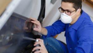 Paint technician is spray a clear coat on the car body.