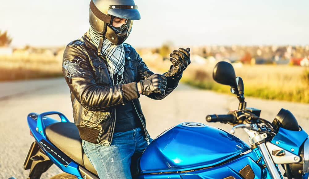 Motorcyclist wearing and fitting the safety gear.