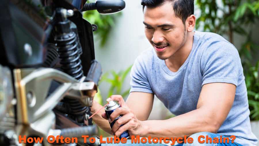Man oiling and spraying motorcycle chain lube.