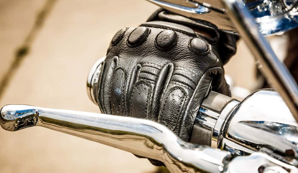 Motorcyclist wearing a thick glove to prevent hand numbness.